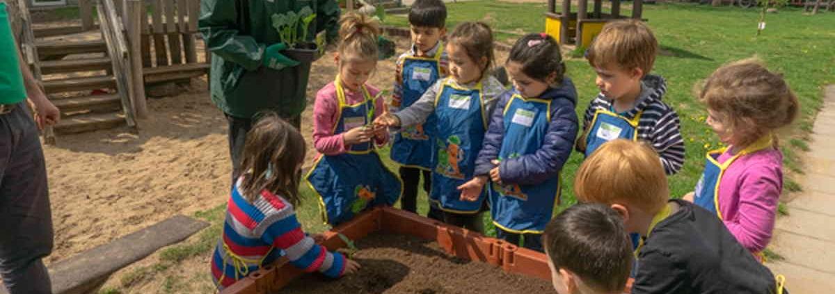 Kinder stehen vor einem Hochbeet und haben Pflanzlöcher ausgehoben