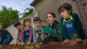 Kinder und Erzieherin betrachten die neuen Pflanzen im Hochbeet