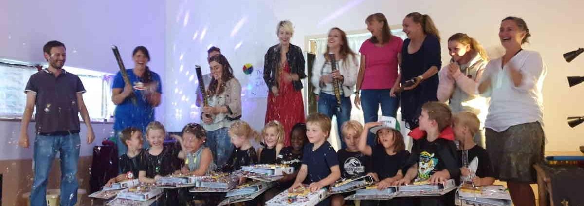 Schulkinder sitzen mit ihren Portfoliomappen auf Stühlchen, Erzieher und Kitaleitung stehen dahinter