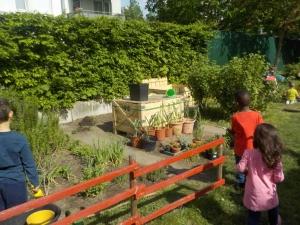 Komposter mit Kindern im Vordergrund
