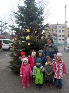 Eine Gruppe von Kindern vor geschmücktem Weihnachtsbaum