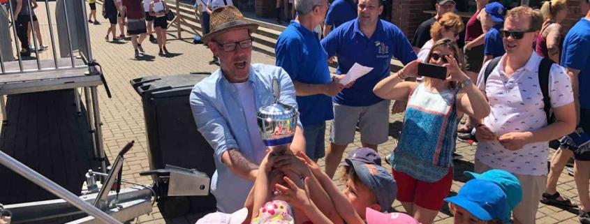 Kinder und Kitaleiter halten stolz den Pokal hoch