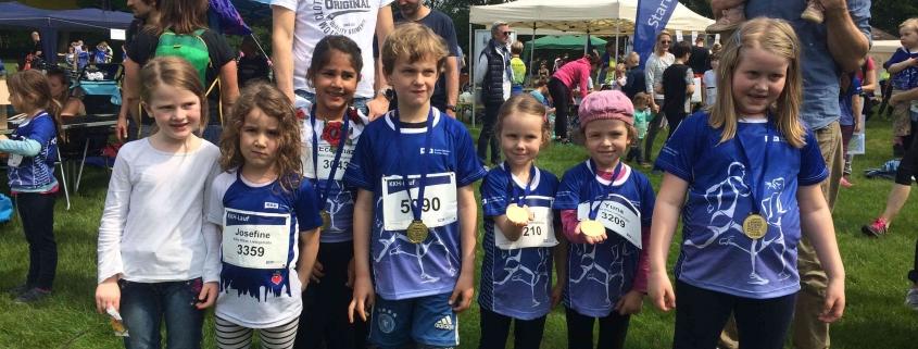 Kindergruppe, die ihre Goldmedaillen um den Hals gehängt haben und glücklich lächen!