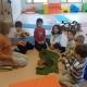 Kinder und Kursleiterin sitzen im Halbkreis auf dem Boden, die Kinder sehen aufmerksam zur Leiterin hin