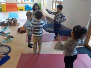 Kinder aus der Yoga-Gruppe stehen auf dem Boden und haben verschiedene Klanginstrumente in der Hand, mit denen sie Geräuschen erzeugen.