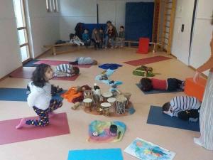 Kinder liegen und sitzen auf ihren Bodenmatten, eine Gruppe Kinder mit Erzieherin im Hintergrund sieht zu
