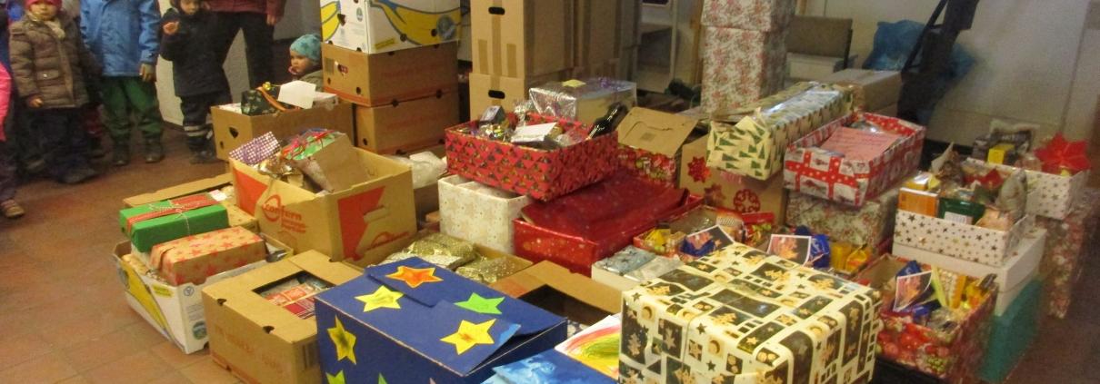Viele weihnachtlich verpackte Pakete zusammengestellt auf dem Fußboden