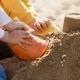 Kinder sielen und und bauen eine große Sandburg